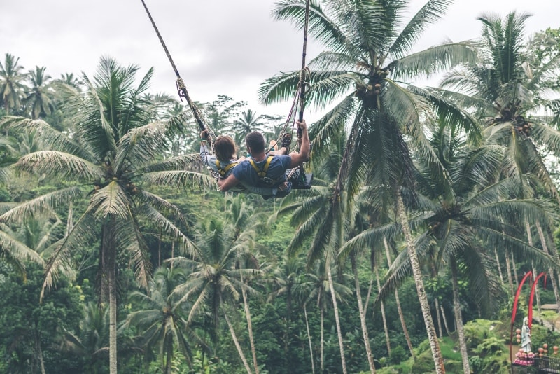 man and woman zip lining near coconut trees