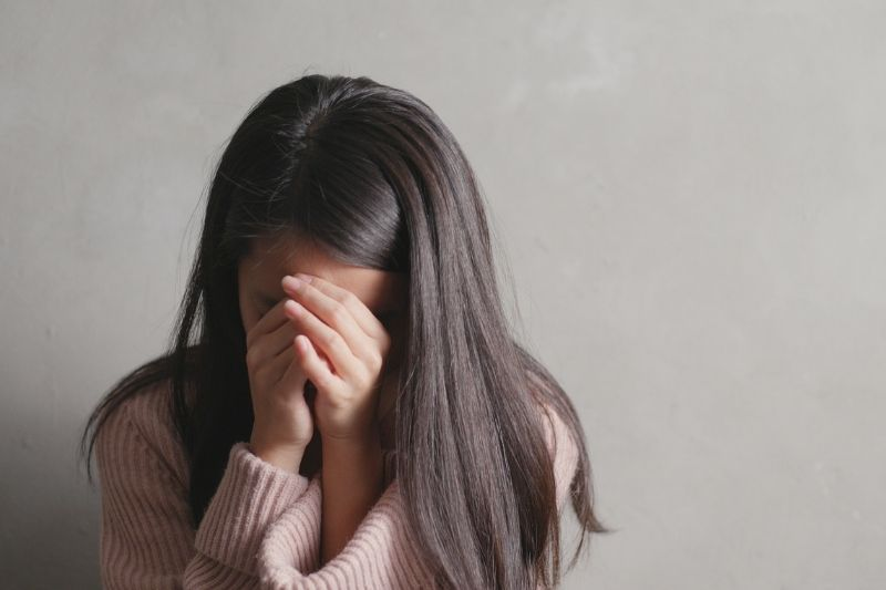 depress young woman crying covering her face