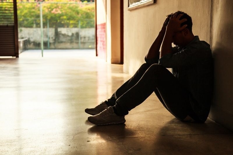 depressed young man sitting on the floor