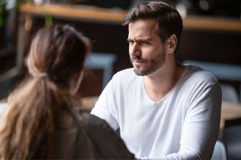 doubting or dissatisfied man during a date with a woman