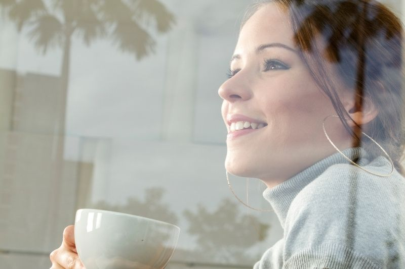 dreamy and happy young woman with a cup in sideview covered with glass wall