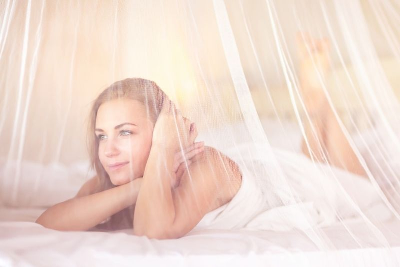 dreamy woman in bedroom with white tender net