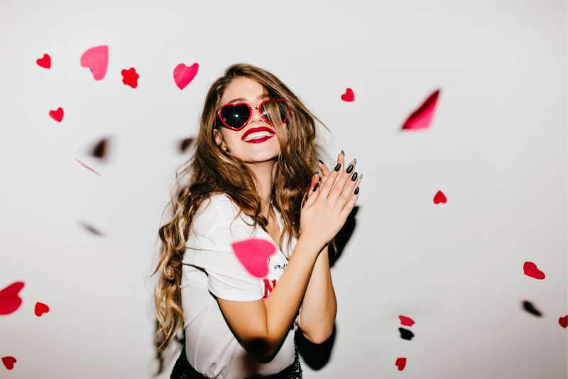 easy going girl expressing positivity with confetti of hearts