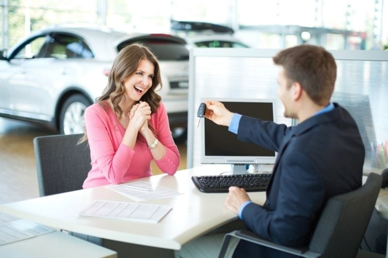 excited woman buying car receiving car key from the dealer