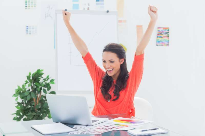 excited woman raising hands inside the office celebrating success