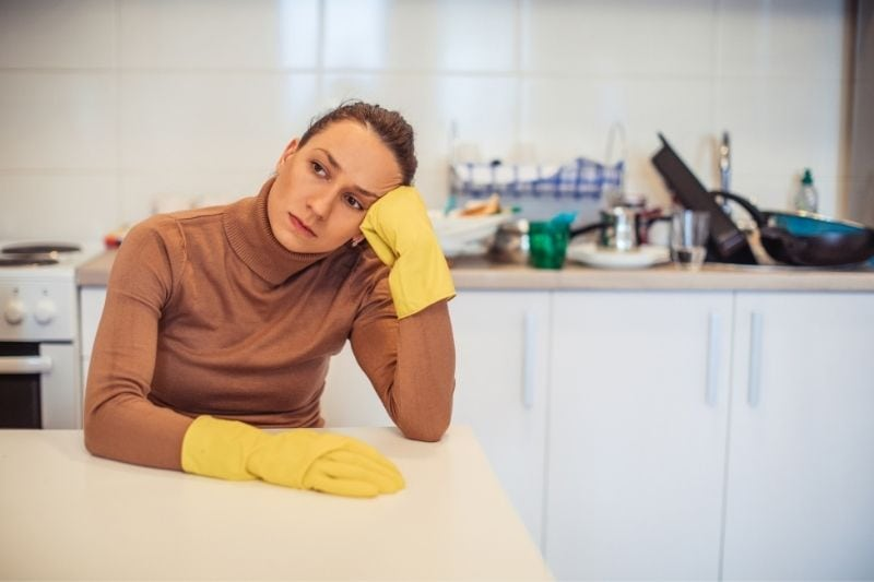 exhausted wife with gloves sitting by the table in the kitchen