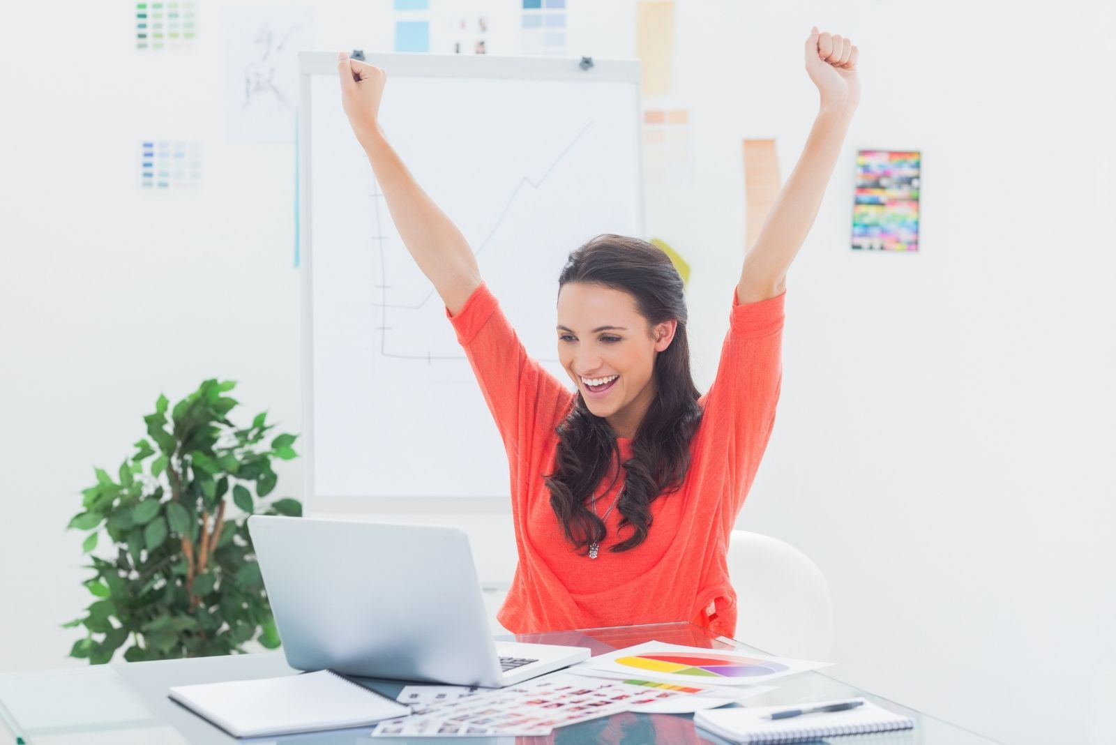 feeling accomplished woman raising her hands while looking at her laptop in her office table