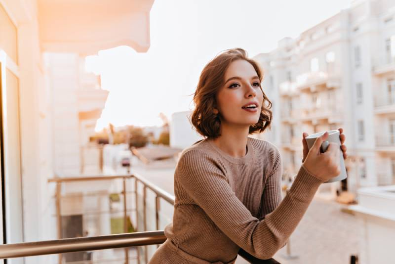 female model holding cup of coffee
