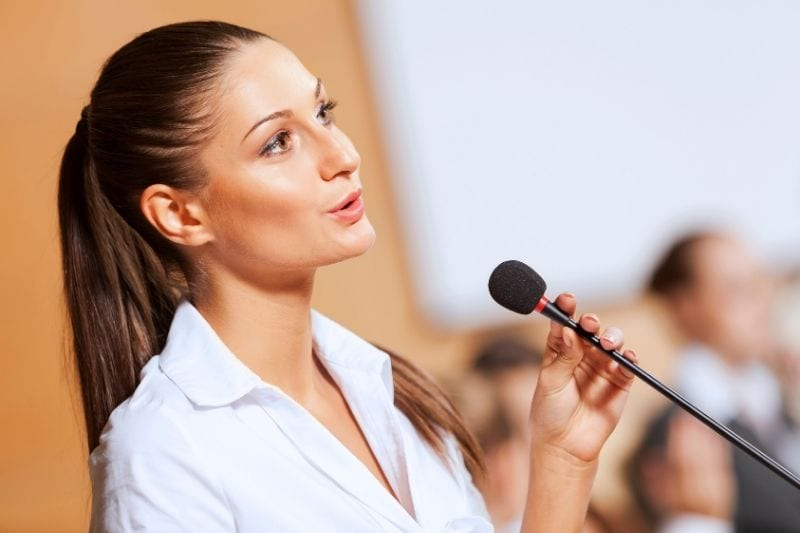 female public speaker talking in a mic with people in blurred background