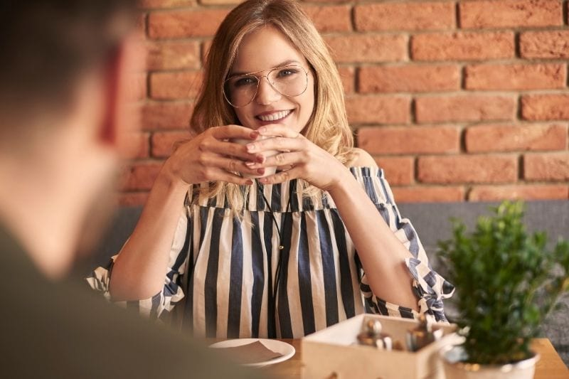 first date with a cup of coffee inside a cafe between a man and a woman