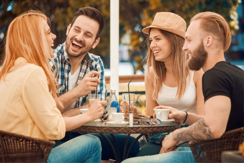 four friends chatting in an outdoor cafe laughing