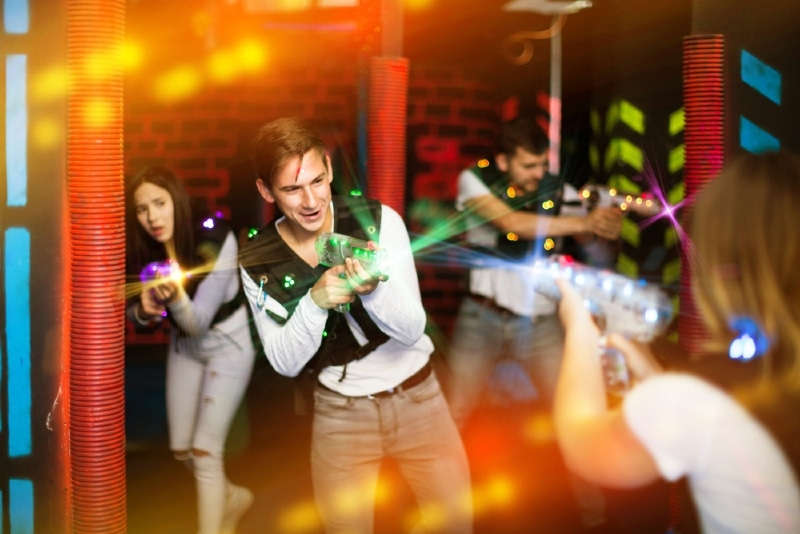 friends holding laser pistols playing laser tag