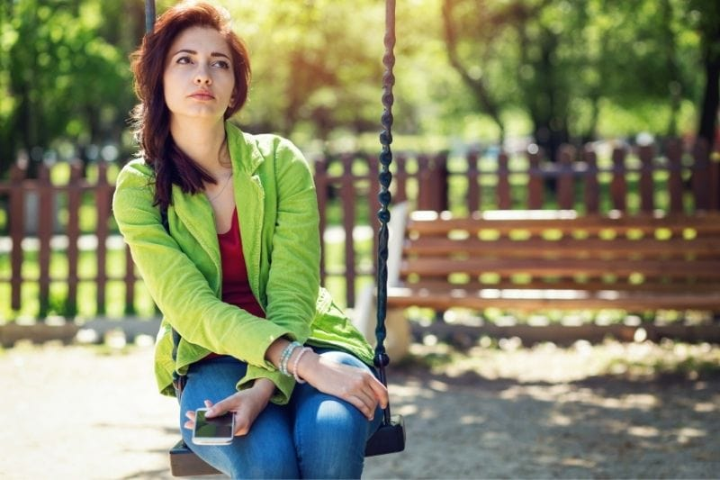 girl sitting on swing holding her phone and thinking