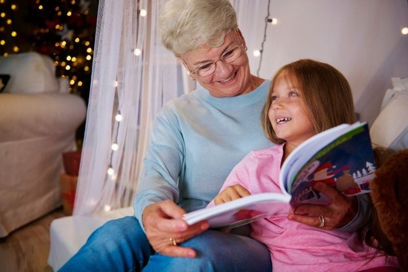 grandmother and granddaughter having good time reading book in the bedroom