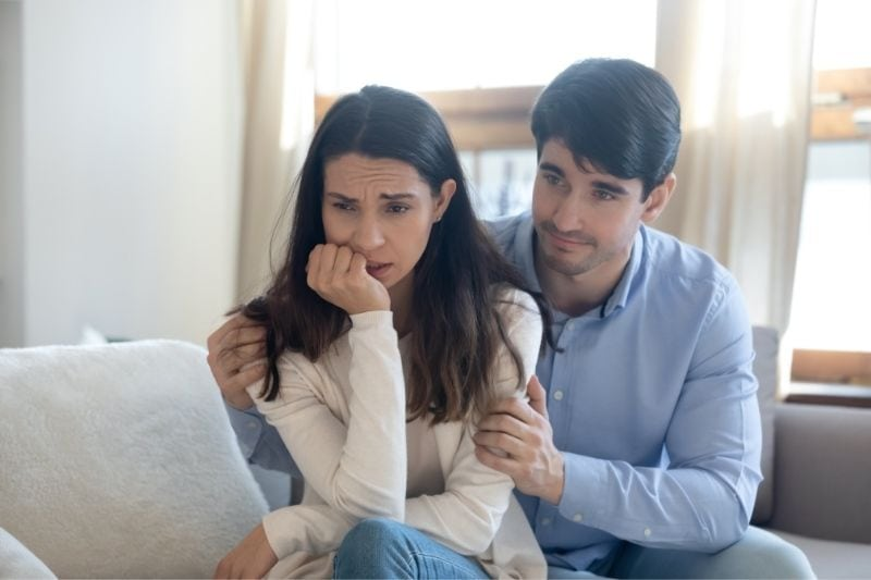 guilty young man saying sorry to an upset stressed woman inside living room