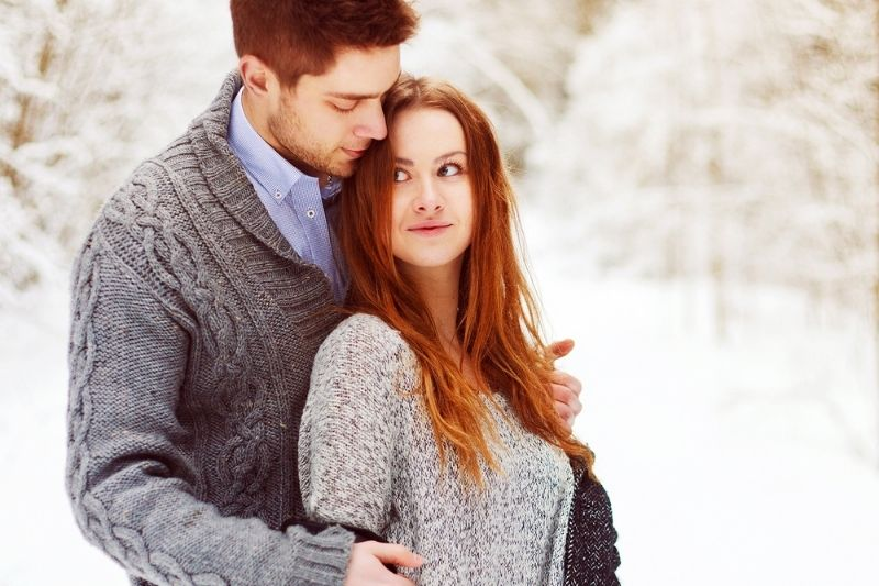 guy hugging woman standing outdoors during winter