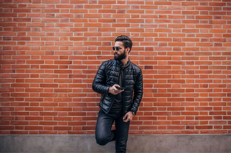 handsome bearded man texting on smartphone while leaning on the brown bricked wall