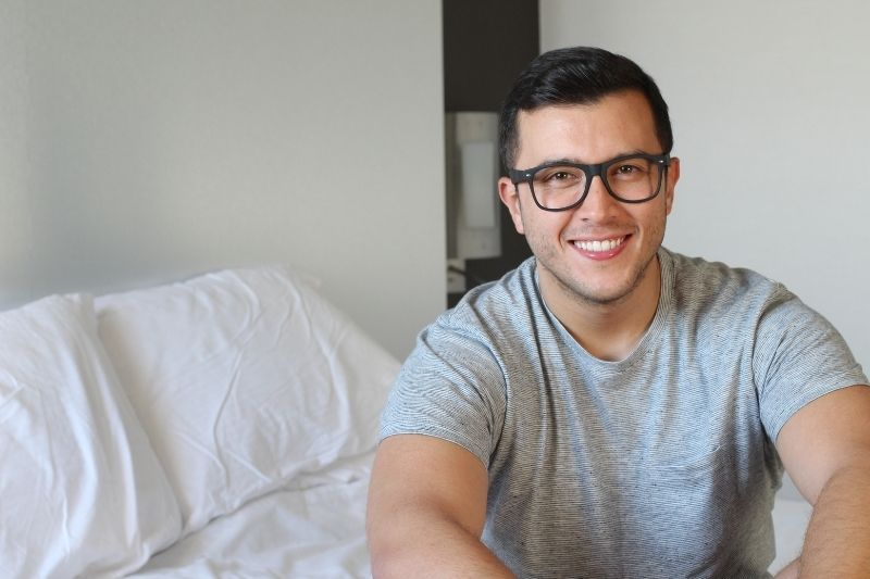 handsome ethnic man smiling at home sitting on bed