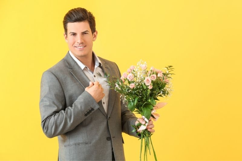 handsome man in suit bringing a bouquet of flower standing against yellow wall