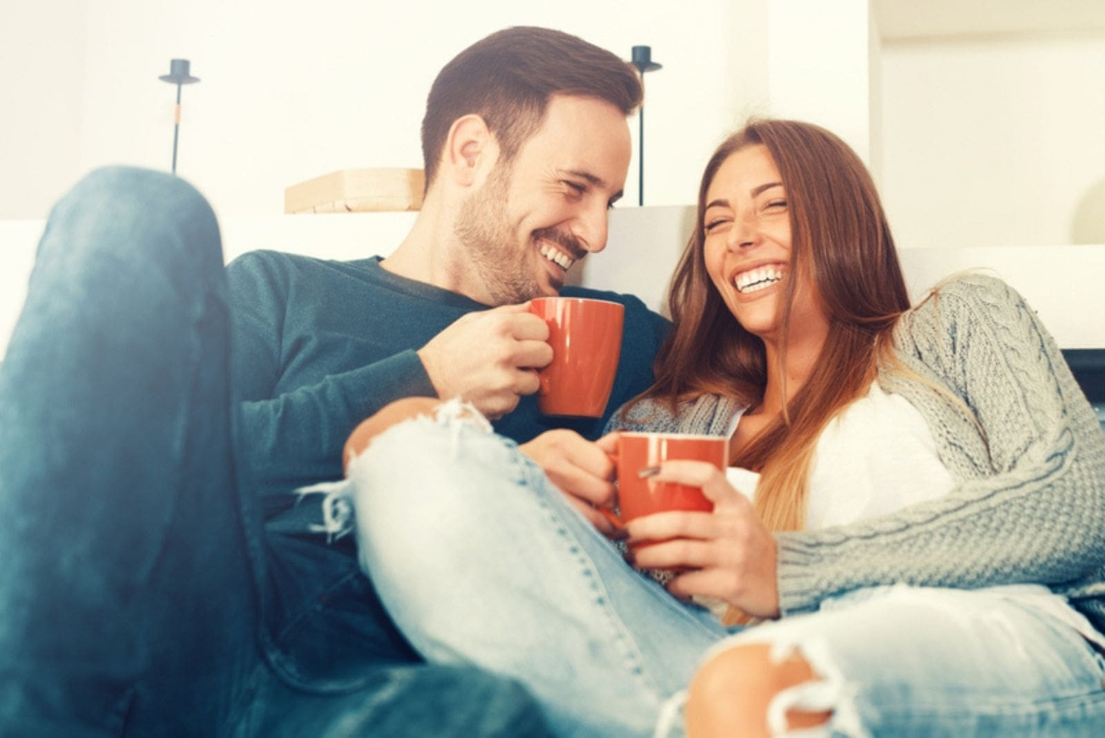 happy couple laughing while drinking coffee and cuddling in the sofa