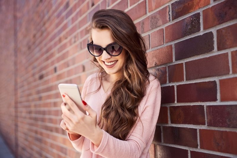 happy woman reading message on her smartphone while standing near a brick wall