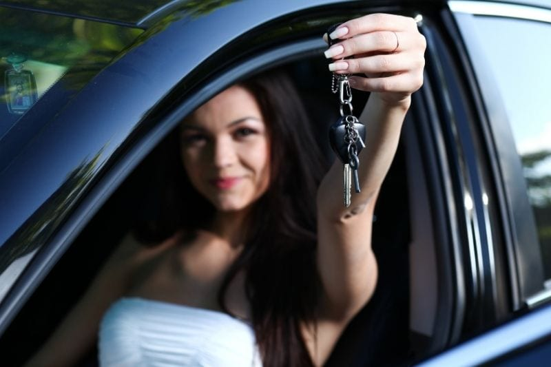 happy young woman brags new car showing car keys