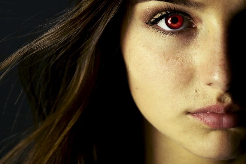 image of a beautiful young vampire woman with red eye cropped half of the face
