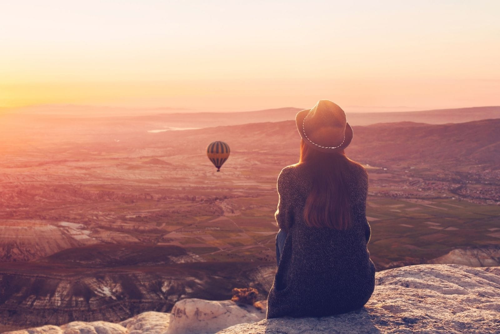 image of woman on top of a mountain admiring the balloons in the air