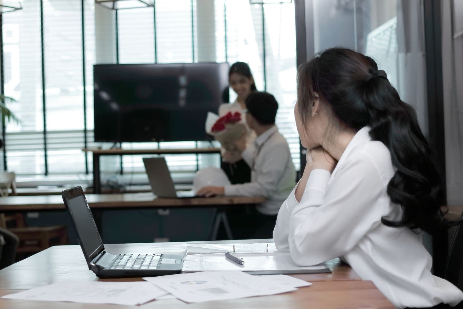 jealous business woman looking at the guy colleague giving flowers to a female colleague