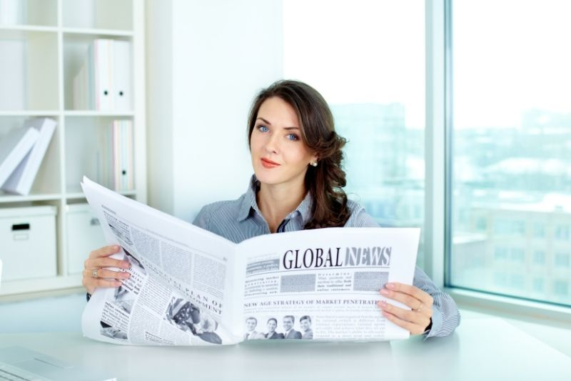 lady boss with a newspaper sitting by her table inside the office