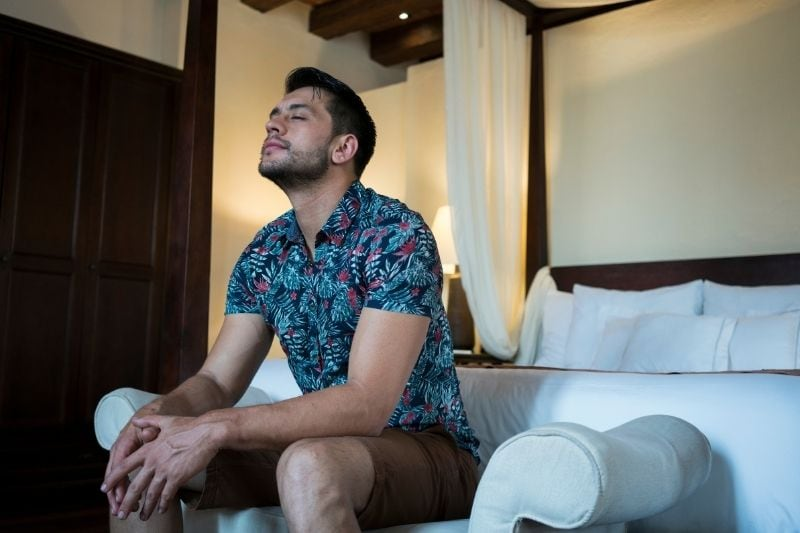 latin man sitting on the edge of the bed of the hotel closing eyes