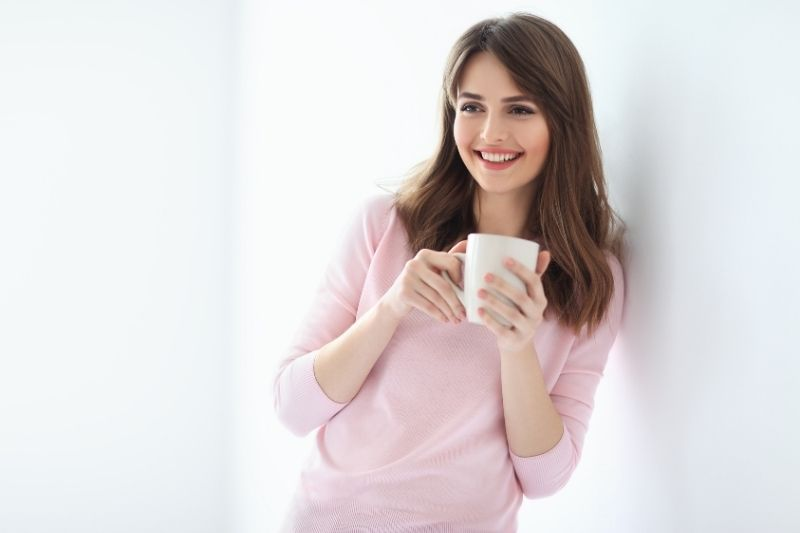 laughing beautiful woman with a mug leaning on a white wall wearing pink sweater