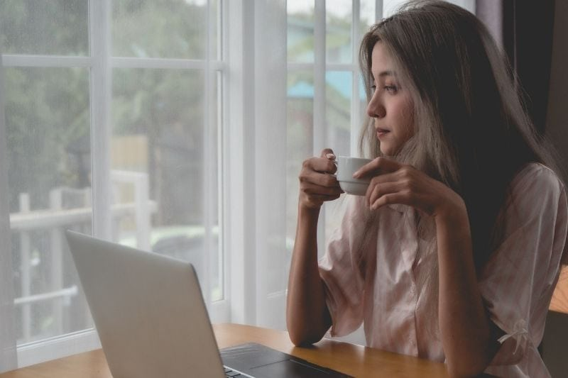 lazy woman drinking coffee in front of her laptop at home in the morning