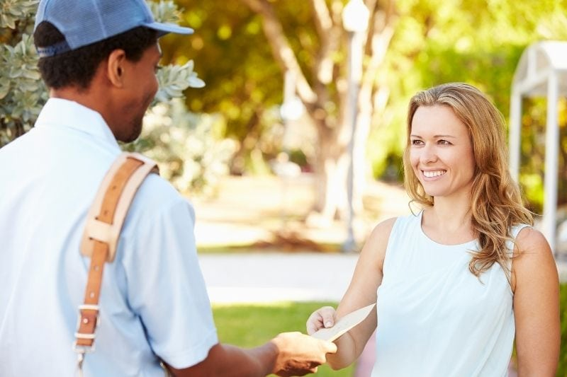 mailman delivering letters on the woman receiving it with a smile outside their house