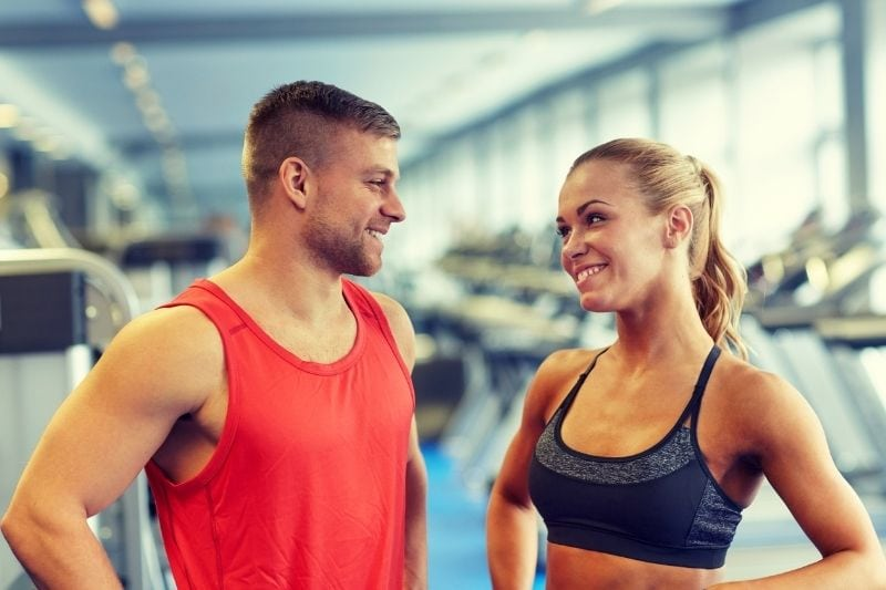 man and woman in gym talking and smilling wearing athletic wear