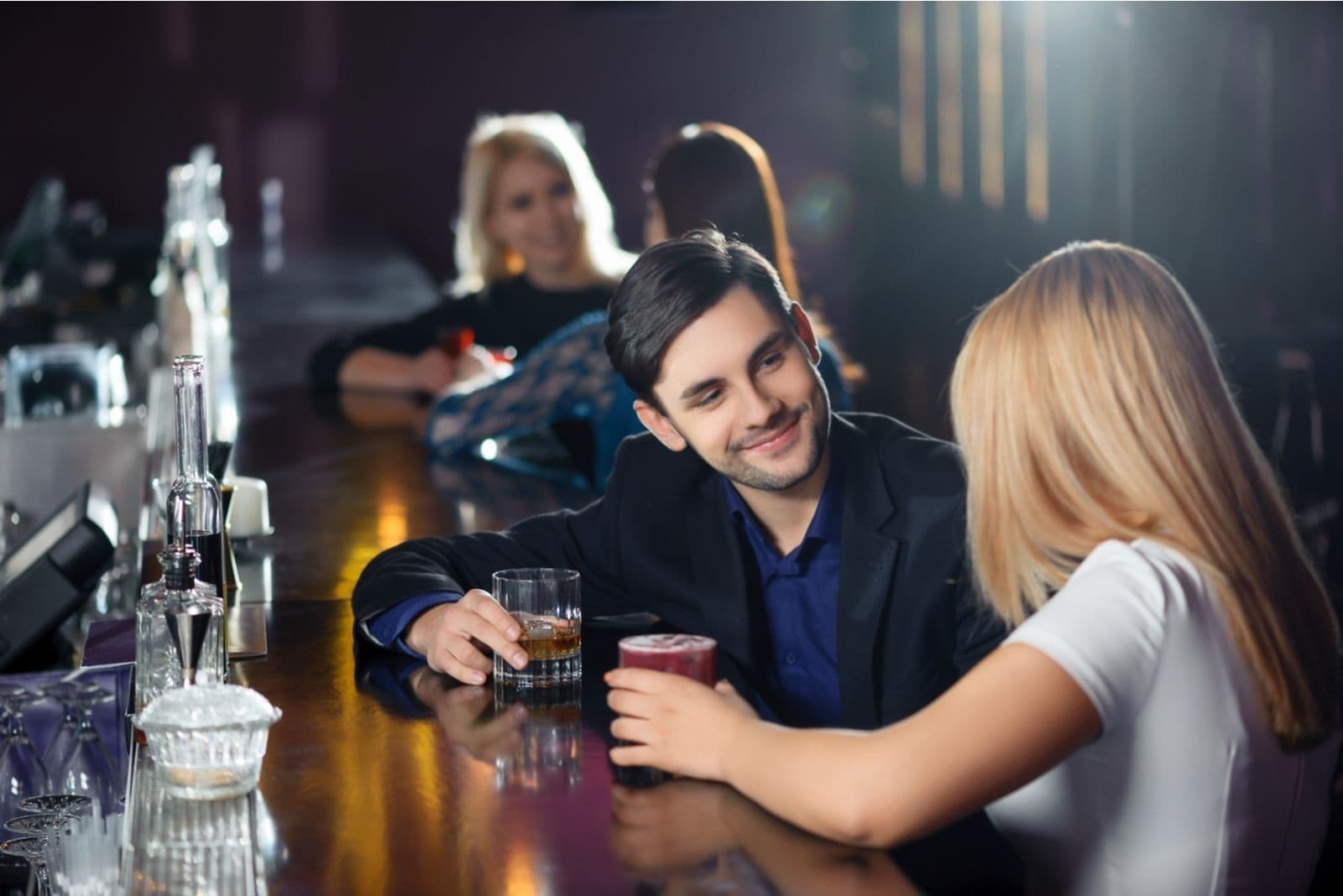 man and woman in the bar having a chat while drinking beer
