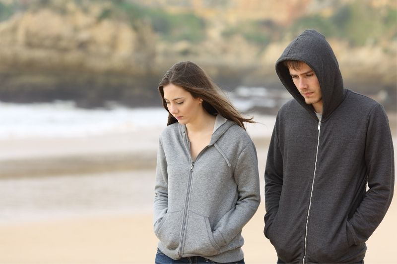 man and woman walking along the beach wearing hoodies with hands inside the pocket