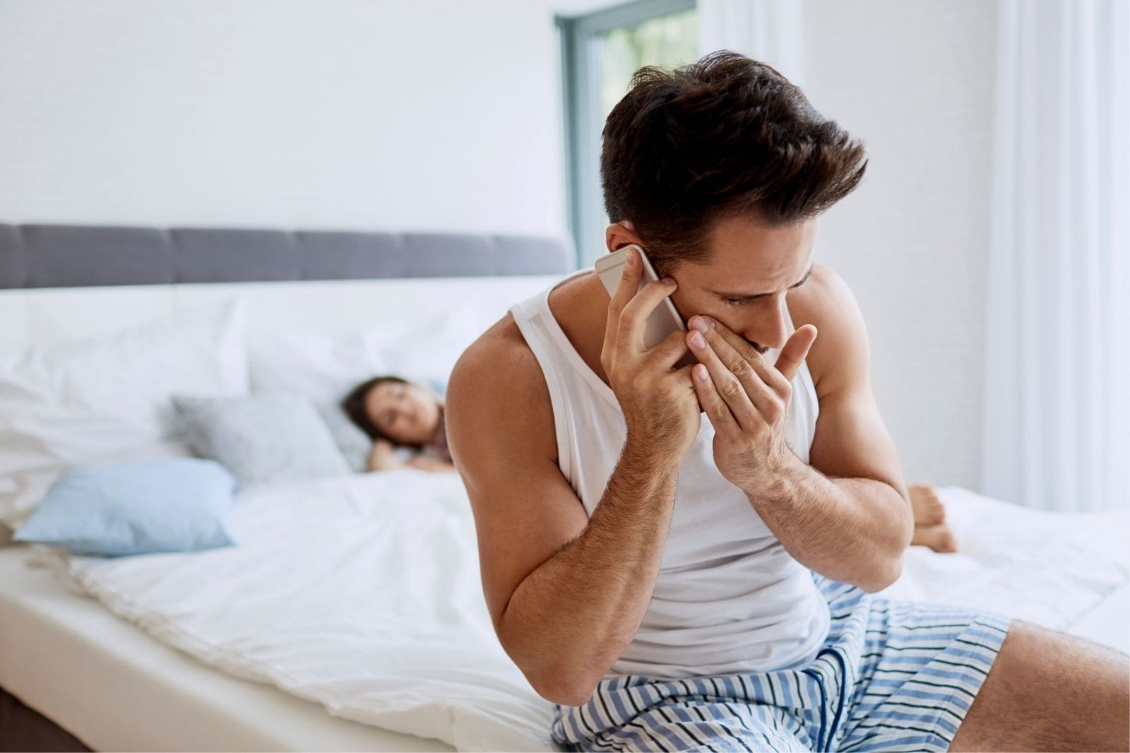man answering phone whispering with wife sleeping on bed