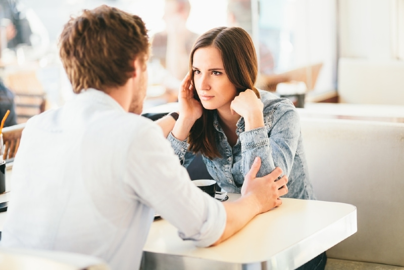 man apologizing to woman while sitting at table