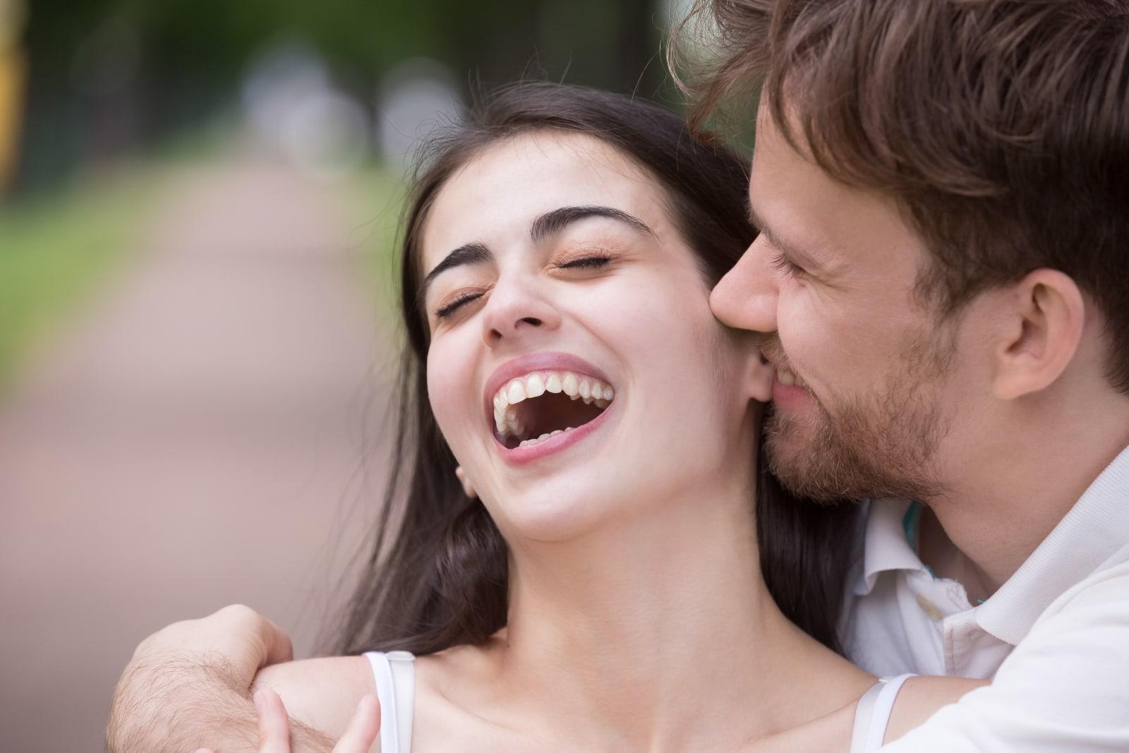 man embrace smiling woman