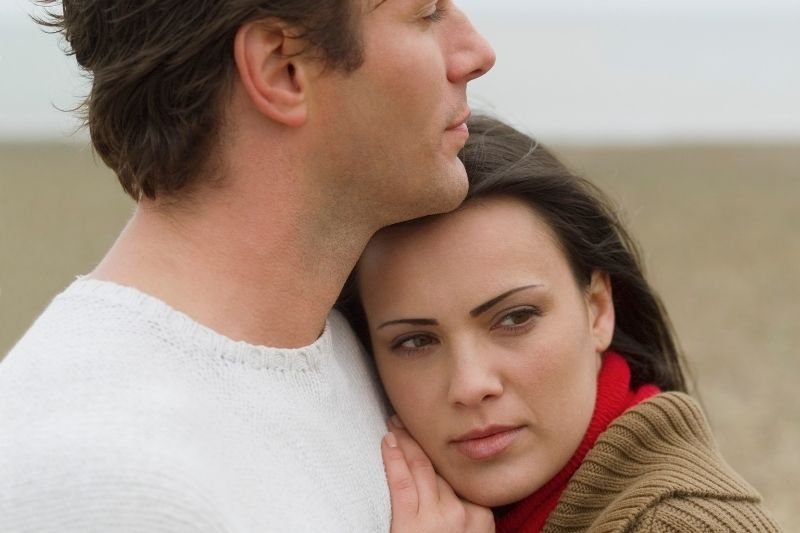man embracing pensive woman leaning on the man outdoors