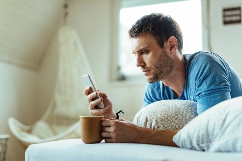 man having coffee on bed while reading his smartphone thoughtfully