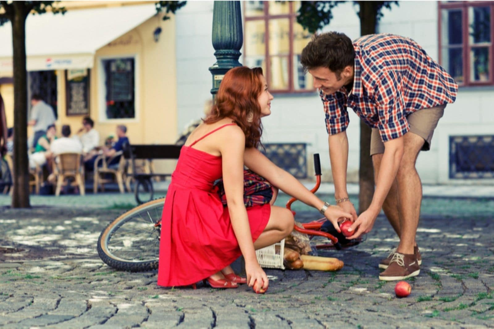man helping a woman get the fruit fell out from the bicycles basket