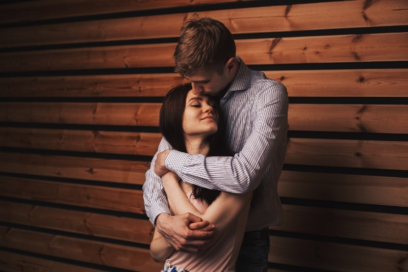 man in striped shirt hugging woman