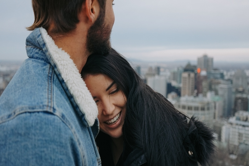man in denim jacket hugging woman on rooftop