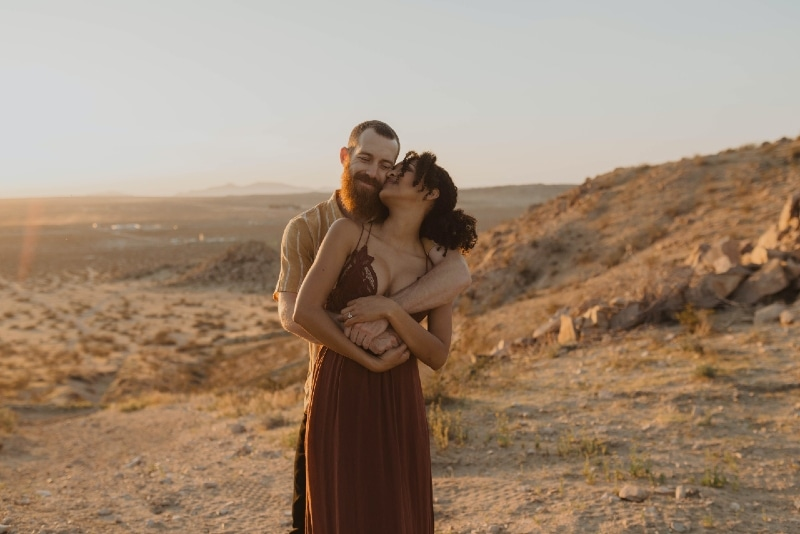 man with beard hugging woman during sunset