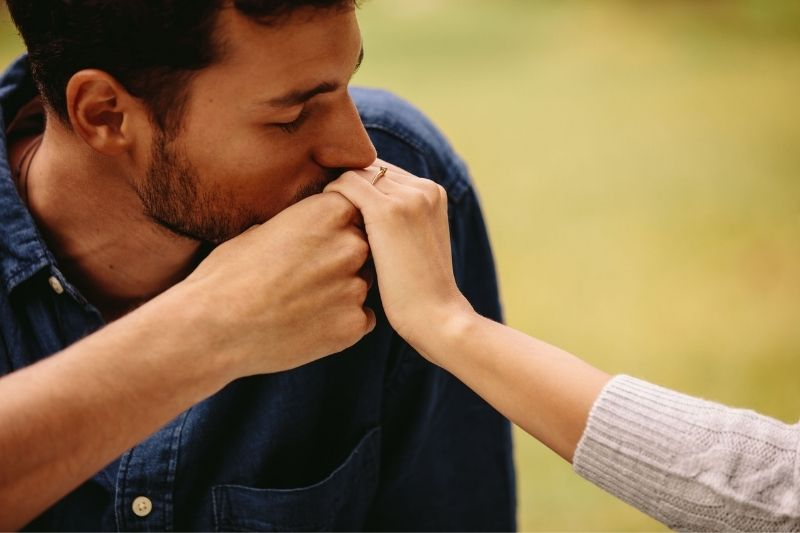 man kissing the hand of a woman wearing an engagement ring