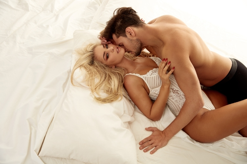man kissing woman's neck while lying on bed