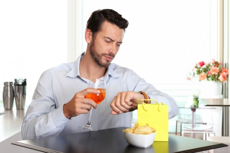 man looking at his watch while sipping a drink inside a restaurant