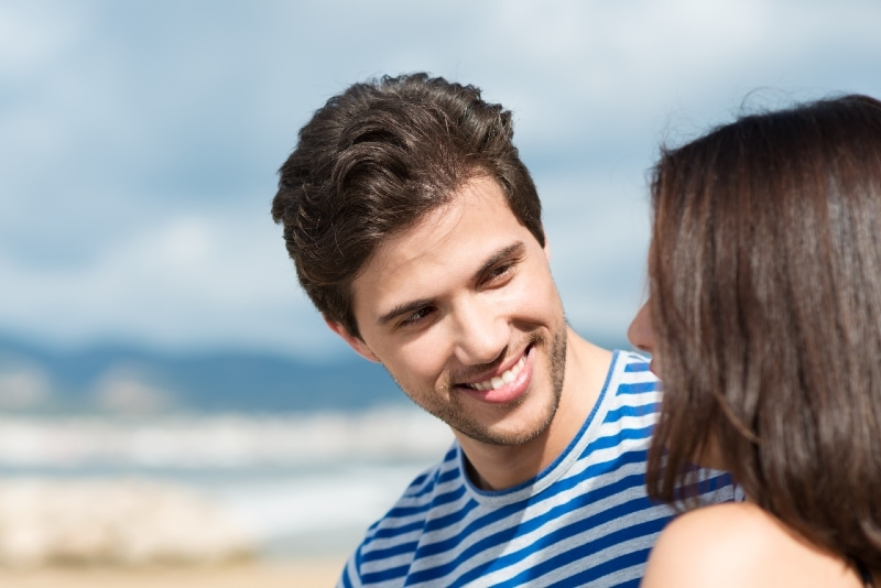 happy man looking at woman while sitting outdoor